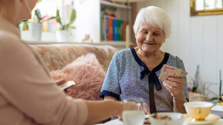 Senior woman and her adult daughter playing cards at home