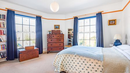 Large double bedrooms with slightly curved walls, sash windows, blue curtains, carpet