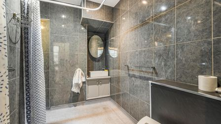 Grey-tiled wet room with slim vanity unit, toilet and square-shaped curtain cubicle with shower curtain