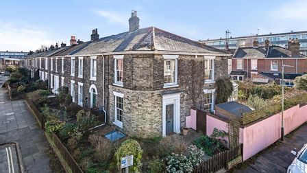 Aerial view of end terrace property with pink boundary wall and slightly curved exterior