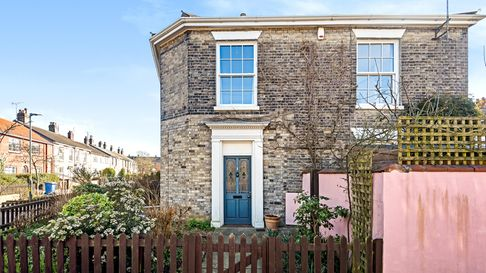 Victorian brick end terrace with path leading up to blue door behind a brown picket fence and pink wall