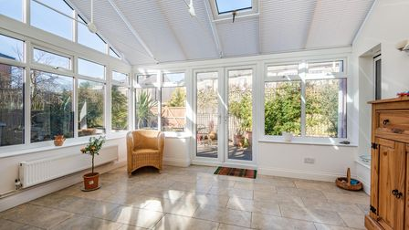 Light-filled glass conservatory with tiled floor and patio doors leading out to courtyard garden