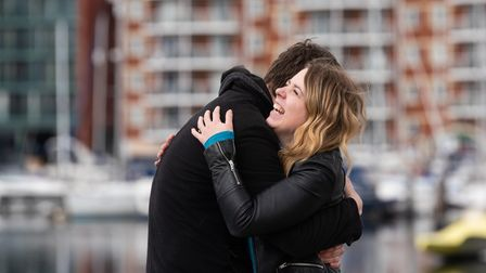 Cameron Smith and Emily Brown hugging on the waterfront
