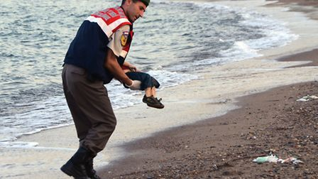 A paramilitary police officer carries the lifeless body of Aylan Kurdi, 3, after a boats carrying hi