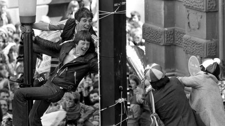 These supporters climbed a lamp post to get a touch of the UEFA Cup as players reached out to them f