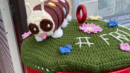 A knitted Colin caterpillar on a Post Box