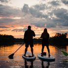A couple paddle boarding on a lake at sunsest