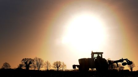 A farmer ploughing his field near Aylsham with the backdrop of a low winter sun