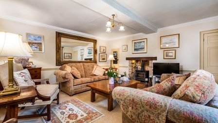Reception room with high ceilings, white beam, two sofas, carpet, large mirror, woodburning stove in hearth