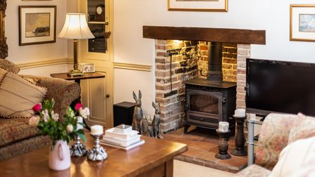 Cosy living room with brick-built hearth and bressumer beam, woodburning stove and antique lamp