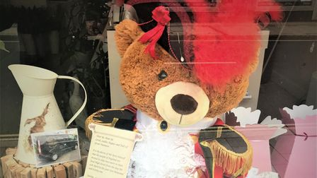 A big teddy bear holds a scroll - he's dressed up like the town crier!
