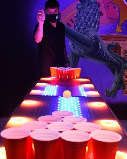 Nuno Pinto, duty manager, plays one of the new games at the Boom Battle Bar, Beer Pong, as the bar r