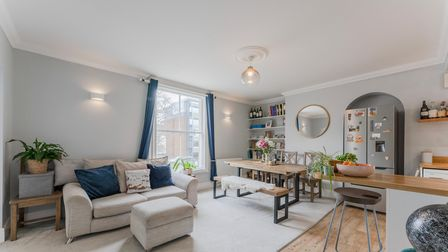 Open-plan living space with breakfast bar, sofa, large sash window, alcove shelving, bench dining table