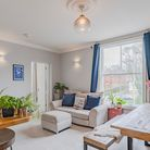 Open-plan living space, large sash window, ceiling rose, bench dining table and breakfast bar with wooden worktop