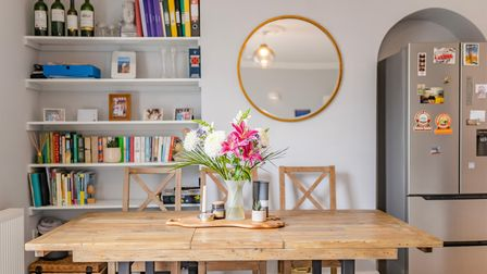 Bench style dining table, alcove shelves, arched recess with refrigerator, circular mirror, vase of flowers