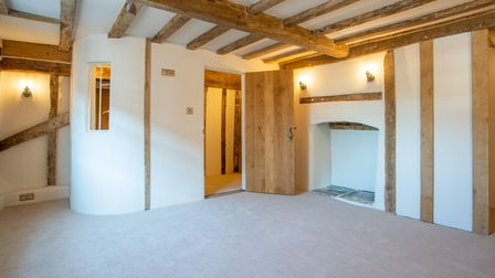 White painted room with heavy wooden door, fireplace alcove, timber beams in wall and ceiling