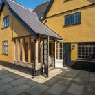 Brick-built period house with yellow colour wash, patio doors opening to paved terrace, restored windows