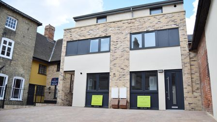 New-build townhouses with brick front, modern windows and driveway with parking out front