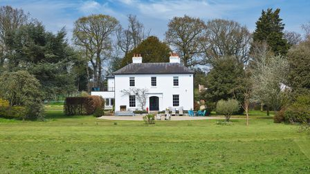 Large white Georgian country house set behind large lawns surrounded by woodland and blue skies