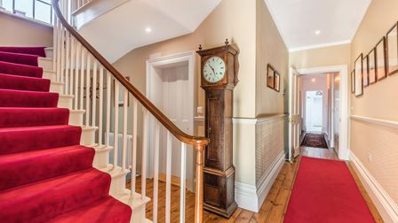 Grand staircase with red carpet runner, wooden floor, entrance hall, grandfather clock
