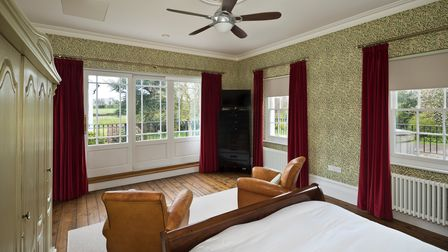 Spacious master bedroom, two armchairs at end of bed, wooden floors, sash windows, botanical wallpaper