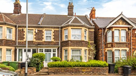 Victorian terrace with two-storeys, bay windows, yellow-painted window frames, ornate brickwork