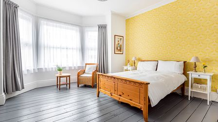 Large double bedroom with yellow wallpapered bed head wall, pine double bed frame, grey painted floorboards