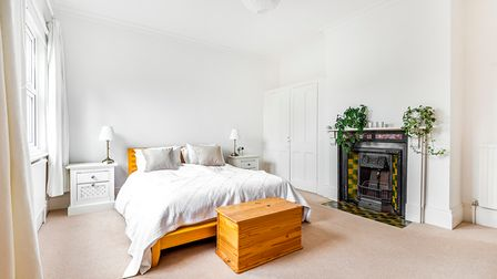 Bright white bedroom space, beige carpet, double bed, pine bed frame, cast iron fireplace
