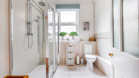 Contemporary white shower room, large walk-in shower cubicle, white tiled floors, toilet, partly tiled walls