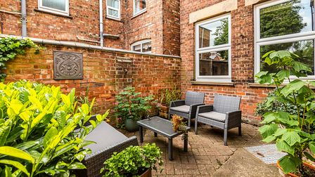 Pretty courtyard garden with outdoor coffee table, two chairs, pots with plants overlooked by two windows