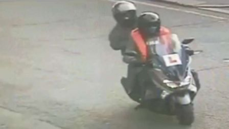 A CCTV image of two men riding a moped