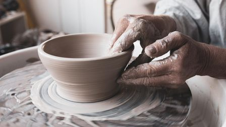 Woman's Hands Shaping Clay into Bowl on Pottery Wheel