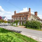 Georgian-fronted brick and flint farmhouse behind white picket fence, gravel driveway with wisteria at the front