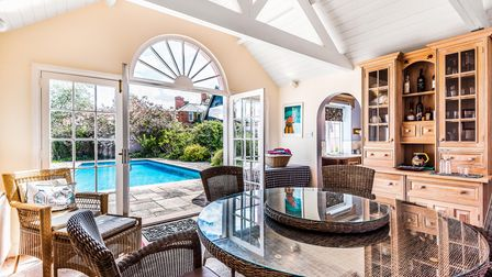 Modern pool house with open doors leading to bright blue swimming pool, kitchen, dining table, tiled floor