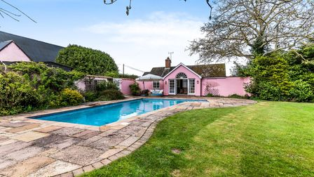 Bright pink single storey pool house with patio doors leading to blue outdoor heated pool surrounded by lawns