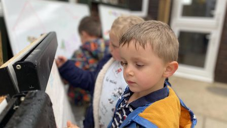 Percy Hughes, age 4, using the easel for drawing