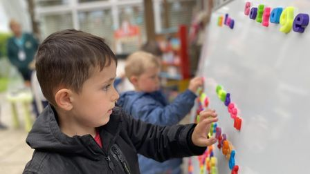 Teddy Riseborough, age 4, using the magnetic letters on the whiteboard.
