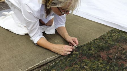 A conservator from the National Trust removing the lining from the rear of the tapestry to prepare i