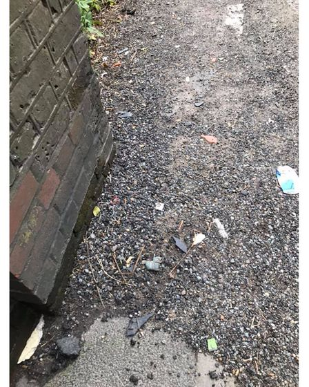 Small shards of broken glass, metal and plastic are left under the bridge on the footpath