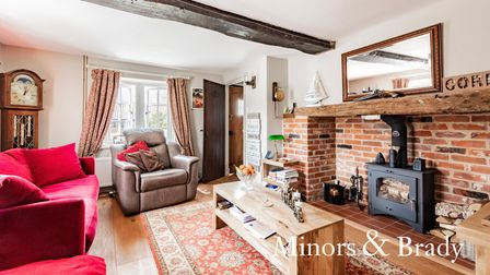 Large living room with brick built hearth, coffee table, chairs, timber ceiling beam, bay window