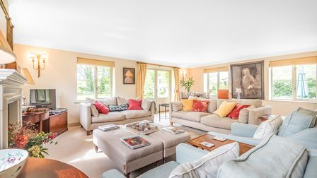 Large living room with three sofas arranged around coffee table, feature fireplace, paintings on wall, lots of windows