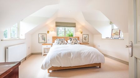 Bright white double bedroom with sloping ceilings, three windows, pine furniture, neutral carpet