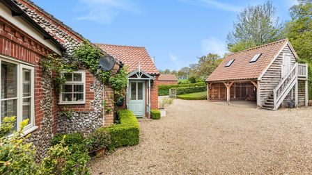 Norfolk flint home with porch and pale green door, shingle driveway, double bay cart lodge