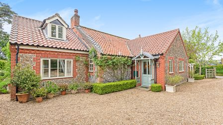 Brick and flint cottage set back off a large shingle driveway with wisteria growing up the side