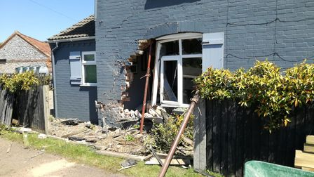 The scene where a car smashed into Aubrey Eke's home in Holt.