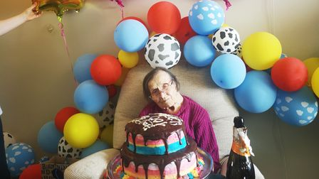 Kathleen Goulson celebrating her 100th birthday with cake and balloons at Cedrus House in Stowmarket