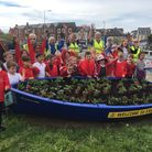 Members of Exmouth in Bloom work with Exeter Road School pupils to add colour to the town