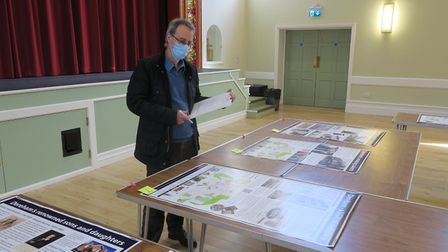 Chair of aboutDereham Mike Webb, inspecting the proofs of the wayfinding signs