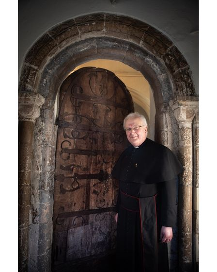 Father John Thackray in front of the door of St Mary at the Elms in Ipswich, which is known to be th