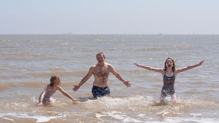 Iona Kelly Benson, Andy Nelson and Daisy Kelly Stevenson cooling off in the sea in Felixstowe. Pict